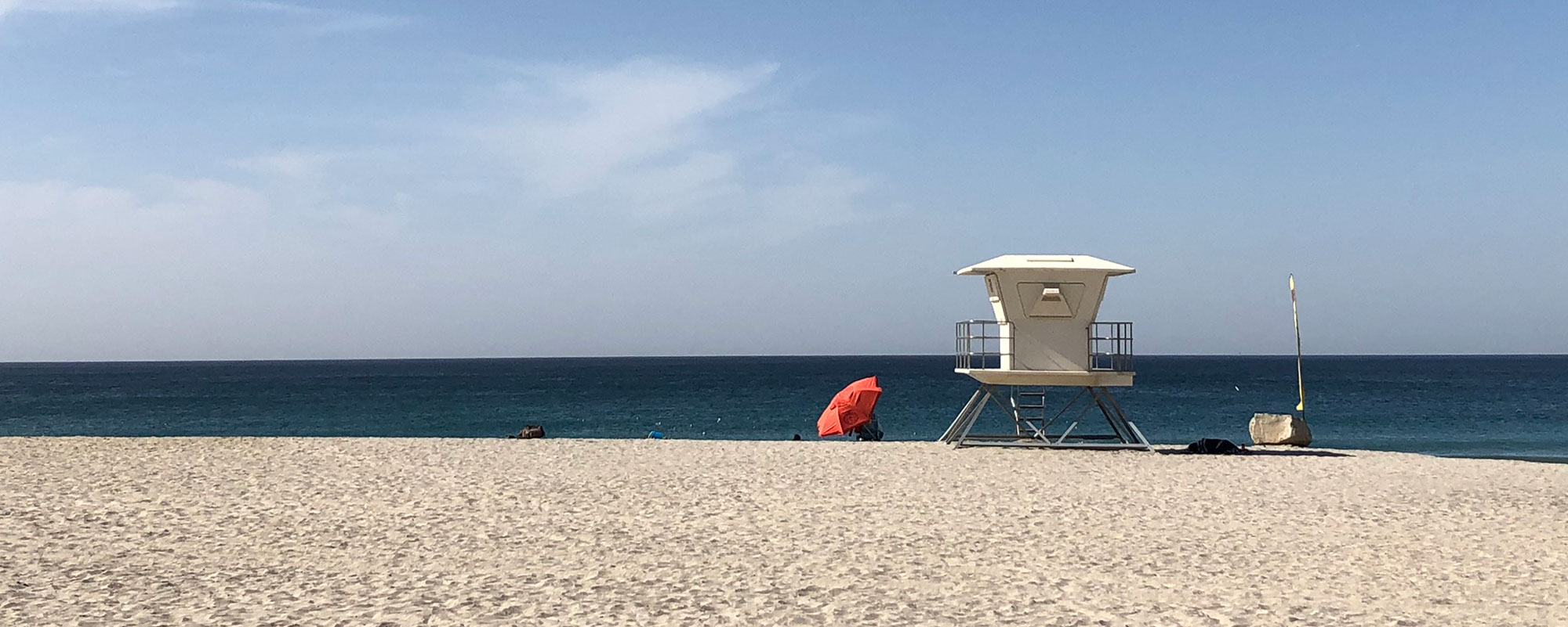 lifeguard tower next to an umbrella on the beach